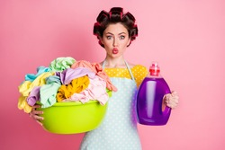 Portrait of her she girlish funky amazed housemaid holding in hands chemical softener laundry stack pout lips isolated pink pastel color background