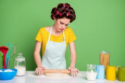 Portrait of her she nice attractive bored sad sullen gloomy housewife cooking delicious pizza rolling dough routine domestic work isolated over green pastel color background