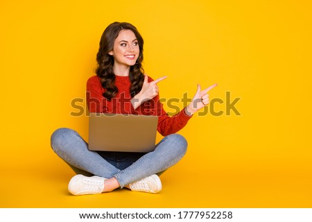Portrait of her she nice attractive cheerful cheery wavy-haired girl sitting using laptop showing idea copy space advert isolated on bright vivid shine vibrant yellow color background