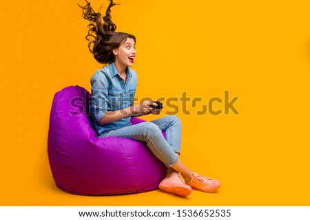 Portrait of her she nice attractive cheerful crazy addicted girlish wavy-haired girl sitting on bag chair playing game air blows hair isolated on bright vivid shine vibrant yellow color background #1536652535
