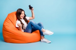 Portrait of her she nice attractive cheerful excited glad wavy-haired girl sitting in chair playing online game win isolated on bright vivid shine vibrant blue teal turquoise color background