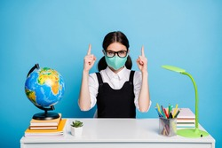 Portrait of her she nice attractive genius brainy diligent girl in reusable mask sitting showing forefingers up copy space ad isolated on bright vivid shine vibrant blue color background