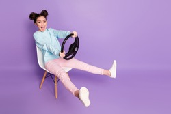 Portrait of her she nice attractive glad cheerful girl sitting on chair holding in hand steering wheel like driving invisible car transport vehicle isolated violet purple lilac pastel color background