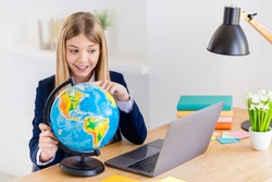 Portrait of her she nice attractive intellectual brainy cheerful small little long-haired girl using laptop learning world political map researching globe countries in light white class room indoors