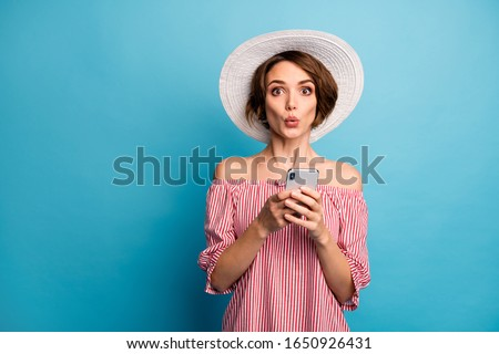 Portrait of her she nice attractive lovely amazed stunned brown-haired girl using online internet app store shopping service isolated on bright vivid shine vibrant blue color background