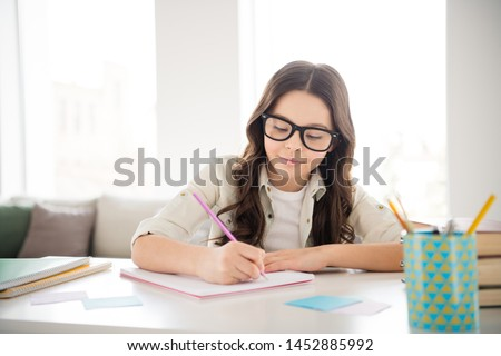 Portrait of her she nice attractive lovely charming cute peaceful confident intellectual wavy-haired pre-teen girl wearing eyewear eyeglasses writing copybook in light white interior room indoors