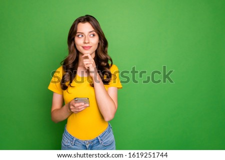 Portrait of her she nice attractive lovely charming winsome cheerful curious wavy-haired girl creating new post smm isolated over bright vivid shine vibrant green color background