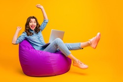 Portrait of her she nice attractive lovely cheerful cheery wavy-haired girl sitting on bag chair celebrating e-commerce breakthrough isolated on bright vivid shine vibrant yellow color background