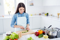 Portrait of her she nice attractive lovely focused brunet girl making cooking fresh tasty yummy salad immunity care culinary hobby in modern light white interior kitchen house stay home