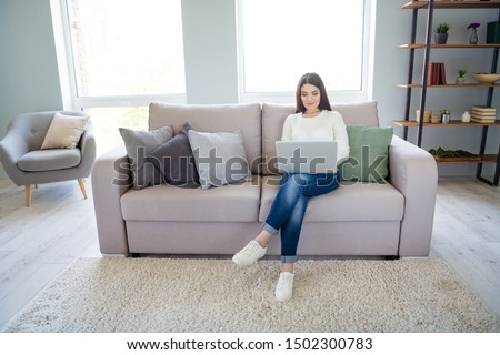 Portrait of her she nice attractive lovely peaceful calm focused clever smart girl making project online using laptop sitting on divan in light white interior living-room indoors
