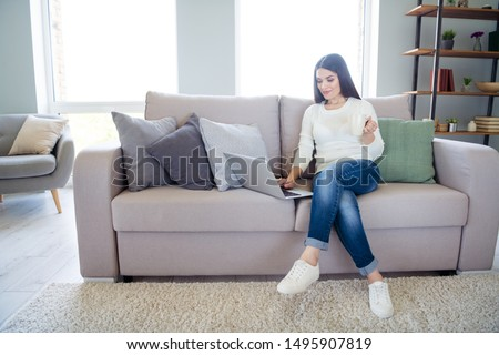 Portrait of her she nice attractive lovely peaceful focused clever smart girl blog blogger making online startup using laptop wi-fi sitting on sofa in light white interior living-room indoors