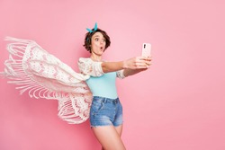 Portrait of her she nice attractive lovely pretty charming amazed cheerful cheery glad positive girl taking making selfie having fun air wind blowing isolated over pink pastel color background
