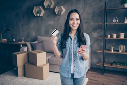 Portrait of her she nice attractive lovely pretty cheerful cheery girl showing plastic card using device app paying buying realestate life insurance in modern loft industrial house apartment
