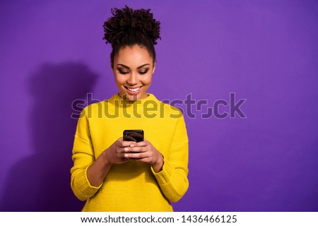 Photo of  Portrait of her she nice attractive lovely winsome focused cheerful cheery wavy-haired girl holding in hands device chatting on web isolated over bright vivid shine violet background