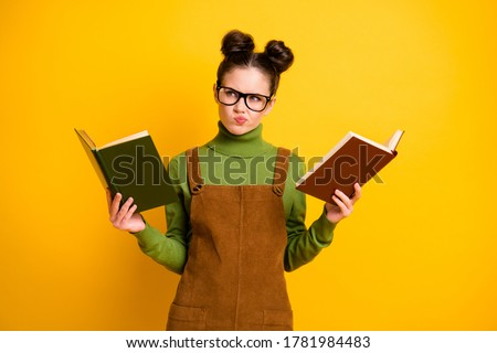 Portrait of her she nice attractive pensive minded knowledgeable girl nerd reading two book compare deciding solving exercise isolated bright vivid shine vibrant yellow color background Stock foto ©