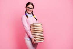 Portrait of her she nice attractive pretty cheerful cheery brainy brown-haired teenage girl carrying holding in hands big pile book science research isolated over pink pastel color background