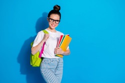 Portrait of her she nice attractive pretty lovely cheerful cheery girl diligent nerd going back to school carrying subject exercise book isolated bright vivid sine vibrant blue color background