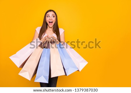 Portrait of her she nice cute charming lovely winsome attractive cheerful cheery straight-haired girl holding in hands new bags purchase win winner isolated on bright vivid shine yellow background #1379387030