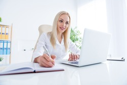 Portrait of her she nice-looking attractive charming cheerful experienced girl doc writing notes plan to-do list patient meds order using laptop in modern light white workplace workstation