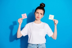 Portrait of her she nice-looking attractive pretty lovely discontent sullen gloomy moody girl holding in hands two different emotion cards isolated on bright vivid sine vibrant blue color background