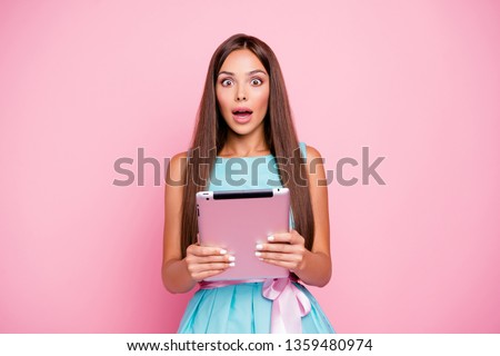 Portrait of her she nice-looking attractive stunning winsome shine elegant cheerful amazed straight-haired lady holding in hands tablet isolated over pink pastel background