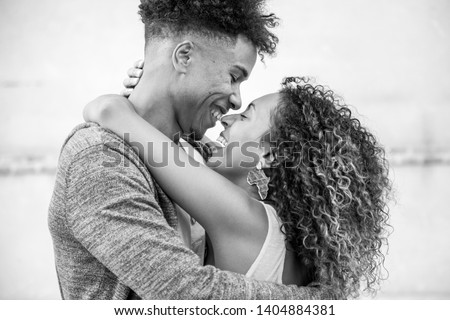 portrait of heterosexual ethnic couple showing affection outdoors #1404884381