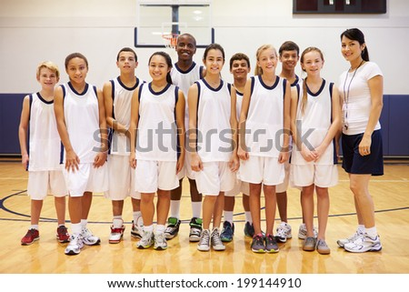 Portrait Of High School Sports Team In Gym With Coach