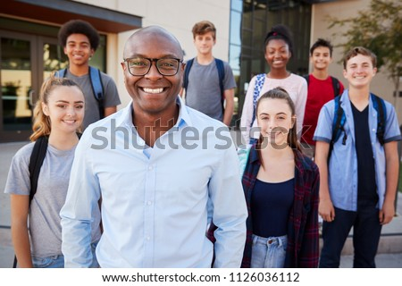 Portrait Of High School Students With Teacher Outside College Buildings