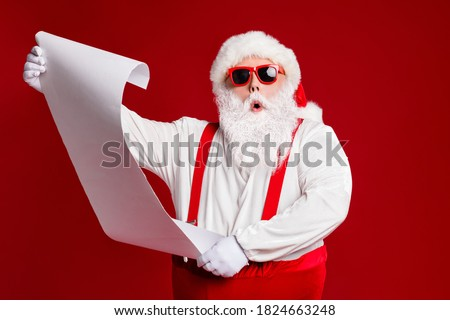 Portrait of his he attractive amazed fat white-haired Santa holding in hands reading wish present gift list pout lips order isolated bright vivid shine vibrant red burgundy maroon color background
