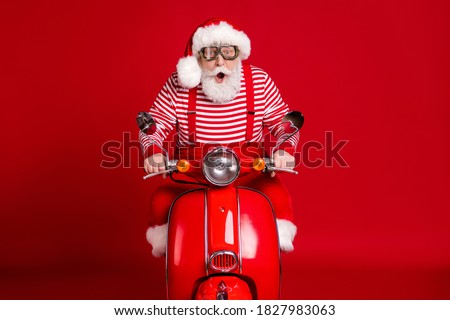 Portrait of his he handsome amazed impressed bearded Santa father riding moped delivering gifts tradition journey fast speed hurry rush isolated bright vivid shine vibrant red color background