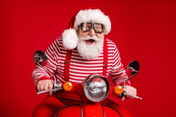 Portrait of his he handsome cheerful cheery bearded Santa father riding moped delivering gifts journey fast speed having fun celebrate isolated bright vivid shine vibrant red color background
