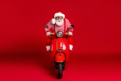Portrait of his he handsome concentrated focused bearded Santa father riding moped North Pole delivery journey fast speed hurry rush trip isolated bright vivid shine vibrant red color background