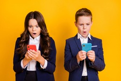 Portrait of his he her she attractive stunned worried outraged small little schoolkids using device browsing fake news post smm blog isolated bright vivid shine vibrant yellow color background