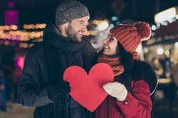 Portrait of his he her she nice attractive charming cute lovely glad cheerful cheery couple wearing warm outfit holding in hands big large heart spending honeymoon 14 February outdoors