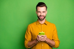 Portrait of his he nice attractive cheerful cheery bearded guy in formal shirt holding in hands digital device 5g app isolated on bright vivid shine vibrant green color background