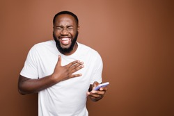 Portrait of his he nice attractive cheerful cheery bearded guy wearing white tshirt reading hilarious funny smm post blog story laughing isolated over dark brown pastel color background