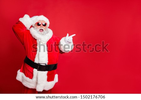 Portrait of his he nice attractive cheerful cheery glad stunned bearded Santa showing ad advert copy space present gift surprise isolated over bright vivid shine red background