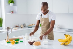 Portrait of his he nice attractive cheerful cheery guy confectioner making fresh bread egg pie hachapuri national culinary confectionery in modern light white interior house kitchen