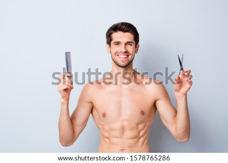 Portrait of his he nice attractive cheerful cheery guy holding in hands hairdress tools scissors and comb hairdresser domestic salon isolated on light white grey color pastel background