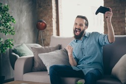 Portrait of his he nice attractive cheerful cheery overjoyed crazy brunet guy sitting on divan playing online game having fun at industrial loft modern style interior room house indoors