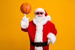 Portrait of his he nice attractive cheerful cheery Santa spinning of forefinger finger orange ball workout activity hobby isolated over bright vivid shine vibrant yellow color background