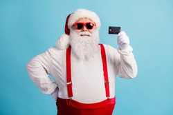 Portrait of his he nice attractive cheerful glad confident white-haired Santa holding in hands credit card order shopping cash back finance isolated bright vivid shine vibrant blue color background
