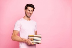 Portrait of his he nice attractive content confident diligent cheerful cheery glad positive intelligent guy holding in hands carrying book library isolated over pink pastel background