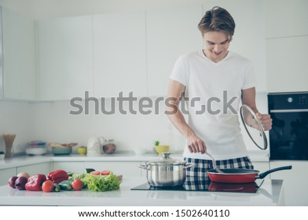 Portrait of his he nice attractive cute cheerful cheery guy frying delicious spicy meat delicatessen at light white modern style interior hotel indoors