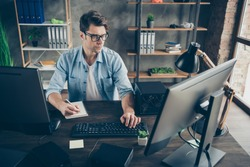 Portrait of his he nice attractive focused experienced geek guy writing plan finance growth programming cyberspace algorithm at modern loft brick interior style work place station indoors