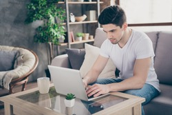 Portrait of his he nice attractive focused skilled experienced guy sitting on divan typing letter email report working remotely at modern industrial loft interior style living-room indoors