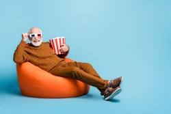 Portrait of his he nice attractive funky cheerful cheery glad bearded grey-haired man sitting in bag chair eating corn watching film having fun isolated over blue pastel color background