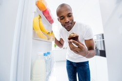 Portrait of his he nice attractive hungry guy looking in fridge taking unhealthy junk fat cupcake cake break pause regime in light white interior house kitchen indoors