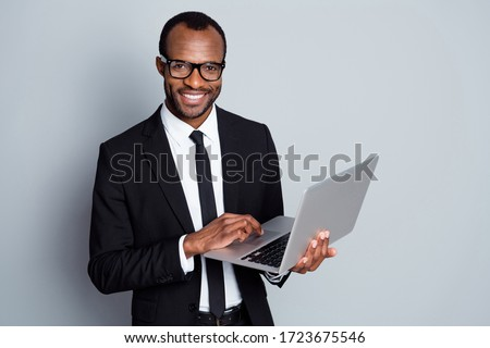 Portrait of his he nice attractive imposing cheerful bearded guy ceo boss chief banker holding in hands digital laptop using e-banking service isolated on grey pastel color background