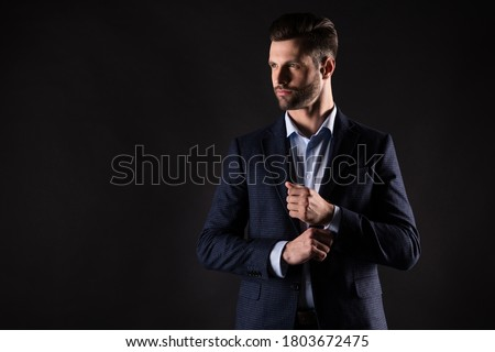 Portrait of his he nice attractive perfect rich wealthy trendy guy corporate partner mr mister fastening button preparing dressing isolated on dark black color background Foto stock ©